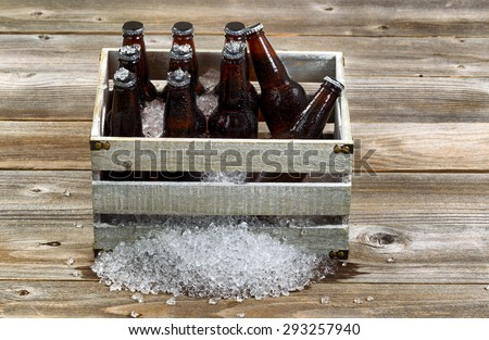 Vintage crate filled with bottled beer and crushed ice on rustic wooden boards.  - stock photo
