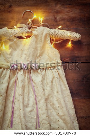 vintage cream girl's dress on hanger with on wooden background with garland lights - stock photo