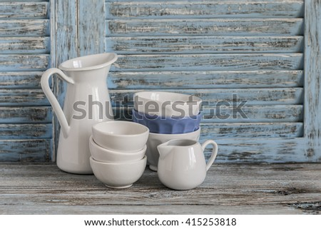 Vintage crockery on a light wooden background. Kitchen still life in rustic style - stock photo