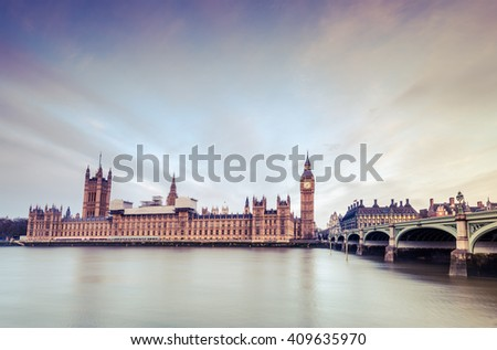 vintage cross processed photo of Palace of Westminster at sunrise, reflection in river Thames - stock photo