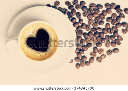 Vintage cup of coffee top view with beans and heart shape made on foam, love concept. Includes clipping path included, so you can easily copy and paste it on your own design. - stock photo