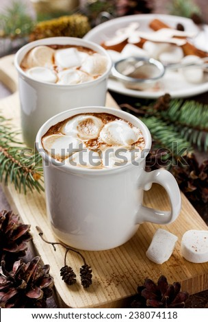 vintage Cup of hot cocoa or hot chocolate with marshmallows on wooden background decorated with spruce, cinnamon sticks and pine cones, christmas concept - stock photo