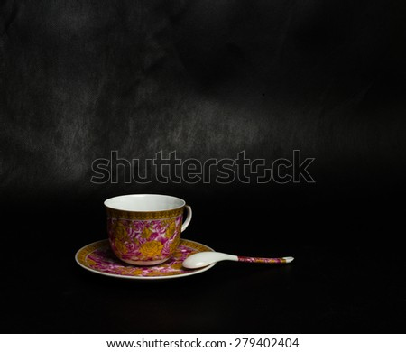 vintage cup, saucer and spoon on a black background - stock photo