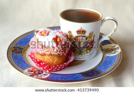 Vintage cup with tea and cupcake decorated with flower - stock photo