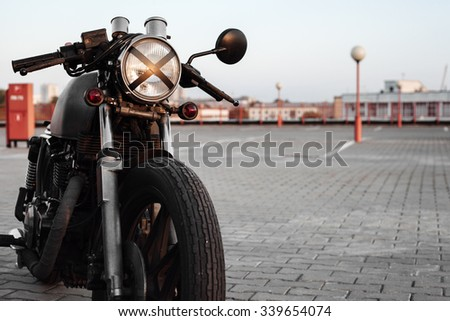Vintage custom caferacer motorcycle in the parking lot during sunset. Stylish motorbike.  Outdoors lifestyle - stock photo
