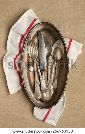 Vintage cutlery on a metal tray with a napkin (red line) - stock photo