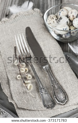 Vintage cutlery on rough napkin, willow twigs and quail eggs in a glass bowl