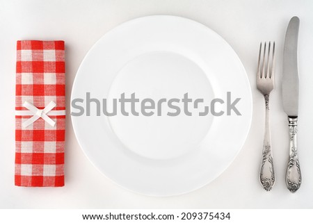 Vintage cutlery set with plate and red checkered napkin. Overhead view. - stock photo