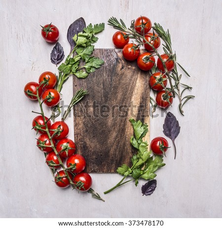 Vintage cutting board with herbs and vegetables on wooden rustic background top view close up place for text,frame - stock photo