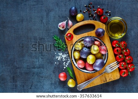 Vintage cutting board with organic ingredients (potatoes, tomatoes, garlic and olive oil) over dark grunge background, top view. Raw vegetables from garden for healthy cooking. - stock photo