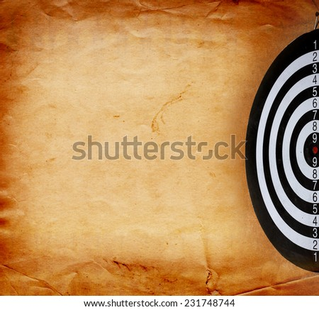 Vintage dart board on dark wall grunge - stock photo