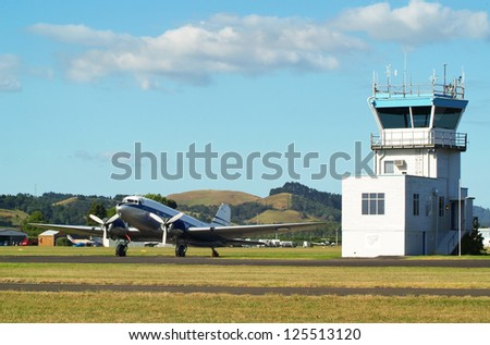 Vintage DC3 aircraft and control tower in Ardmore, New Zealand - stock photo