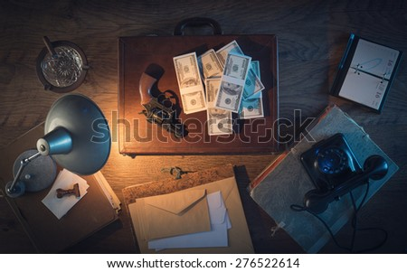 Vintage desktop in the dark with a gun, a briefcase and a lot of dollar packs, top view - stock photo