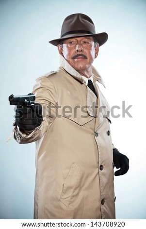 Vintage detective with mustache and hat. Holding gun. Studio shot. - stock photo
