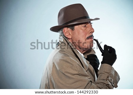 Vintage detective with mustache and hat. Smoking pipe. Studio shot.