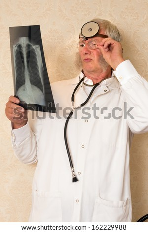 Vintage doctor examining an x-ray in his clinic - stock photo