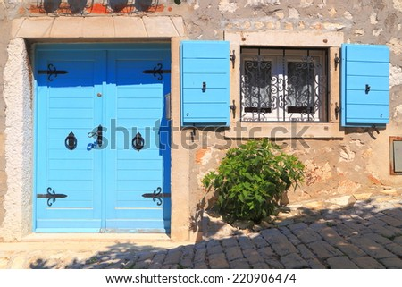 Vintage door and window with wood shutters wide open on sunny street of Mediterranean town, Rovinj, Croatia - stock photo