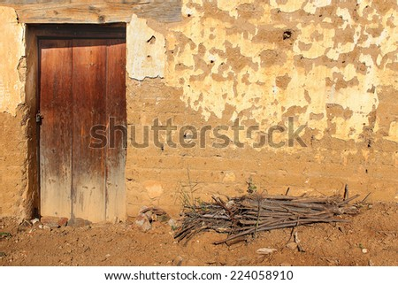 Vintage door on Adobe Facade. Wooden front door of a home. Front view of a weathered Oaxaca adobe brick house with a small pile of sticks for burning as fuel set in earth in front. Horizontal shot. - stock photo