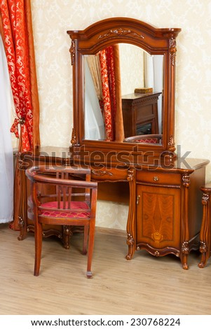 Vintage dressing table and a chair in front of it - stock photo