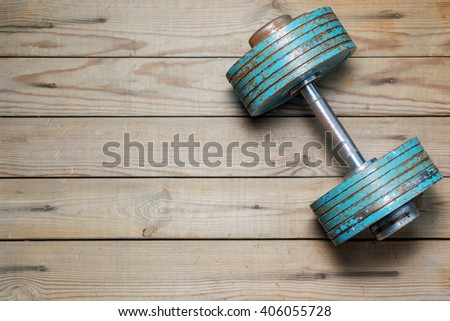 Vintage dumbbell on the wooden floor - stock photo