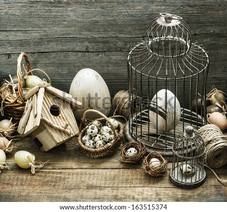 vintage easter decoration with eggs, birdhouse and birdcage. nostalgic country style home interior - stock photo