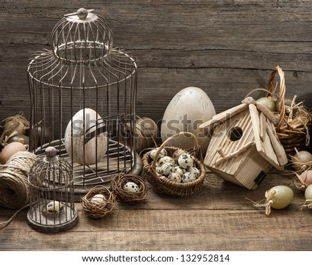 vintage easter decoration with eggs, birdhouse and birdcage. nostalgic still life home interior. wooden background - stock photo