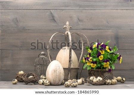 vintage easter decoration with eggs, pansy flowers, nest and birdcage. shabby chic still life - stock photo