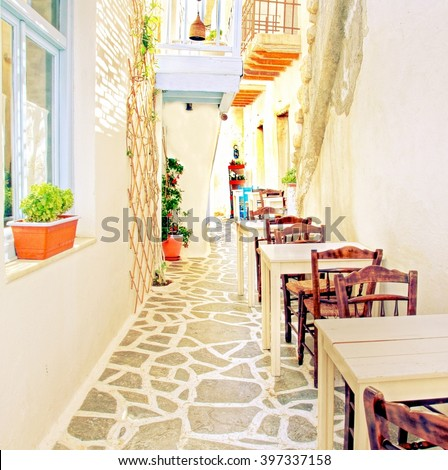 vintage edited image from a sunny cobble stone street at the Cyclades  Island of Mykonos, Greece  - stock photo