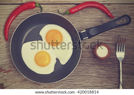 Vintage efekt. Fried egg in a frying pan on a wooden background. - stock photo