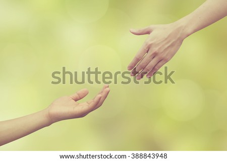 vintage effect of couple helping/pray human hand on blurred green nature background,spiritual of life ideal.support of humanity:love together:heal/help/assistance concept.reach connection:nice friends - stock photo