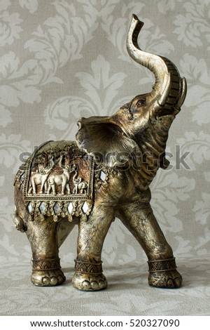 Vintage elephant statue on the textile background.