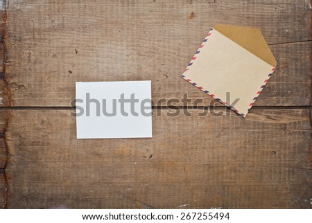 vintage envelope and card on wooden background - stock photo