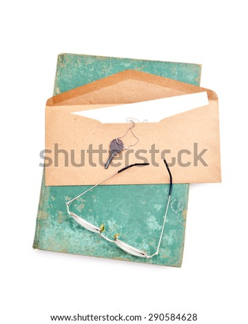 vintage envelope with success key , notebook and glasses on white  - stock photo