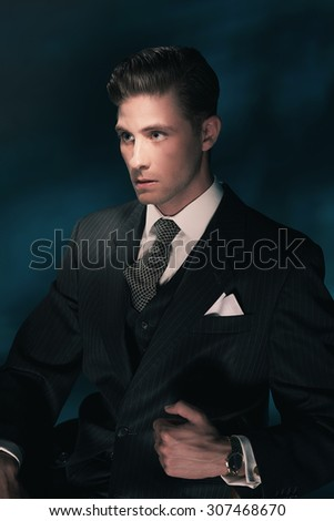 Vintage fashion dandy man in suit and tie sitting on chair. Hair combed back. Dark blue background. Studio shot.