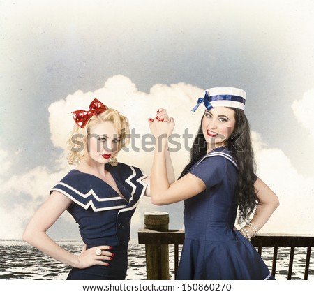 Vintage fashion fight. Beautiful young women with pinup hairstyle and makeup in an arm wrestle competition outdoors at a retro sea dock - stock photo