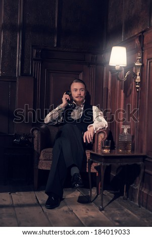 Vintage 1900 fashion man with beard. Sitting in old wooden reading room. Calling with telephone.