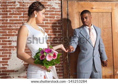 Vintage fashion romantic wedding couple in old urban building. Holding hands. Mixed race.