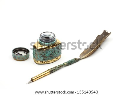 Vintage feather quill and inkwell over white background - stock photo