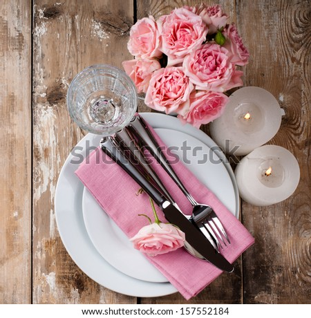 Vintage festive table setting with pink roses, candles and cutlery on an old wooden board - stock photo