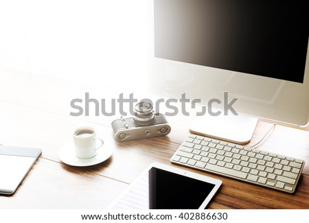 Vintage film camera and the latest technology. Elevated view of a photographer / graphic designer desk with added sun flare.  High resolution image - stock photo