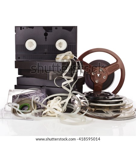 Vintage film camera rolls, old audio and video casettes with tape and foto strip on white background - stock photo