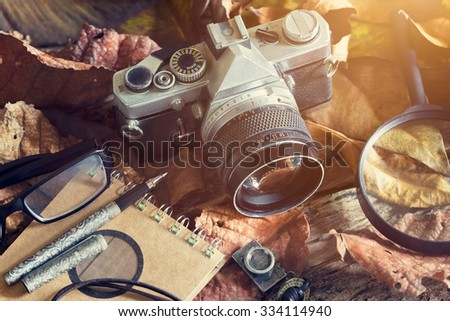 Vintage film camera with dust on dry leaf and wooden in natural background, Vintage color tone
