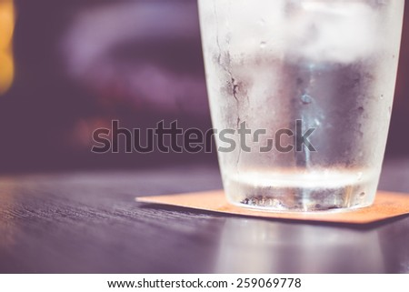 Vintage filter : Cold glass of water on wooden table at restaurant. - stock photo