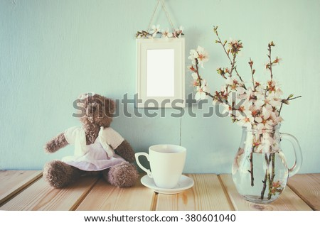 vintage filtered and toned image of cute teddy bear, cup of coffee and blank frame next to spring white cherry blossoms tree - stock photo