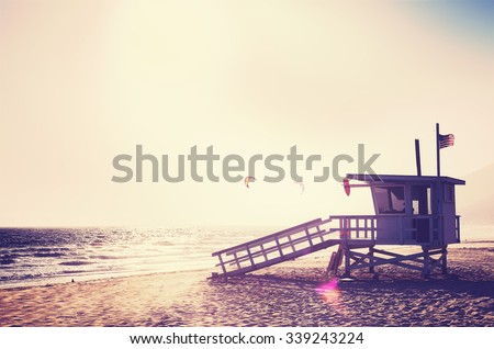 Vintage filtered lifeguard tower at sunset with lens flare effect, USA. - stock photo