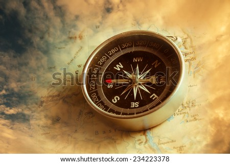 Vintage filtered of compass with dramatic sky background. - stock photo