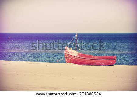 Vintage filtered photo of an old abandoned boat on the beach. - stock photo