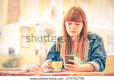 Vintage filtered portrait of serious pensive young woman with smartphone - Hipster girl using mobile smart phone while drinking coffee - Concept of human emotions - Soft focus on sad worried face - stock photo