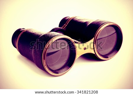 Vintage filtered retro binoculars over white background