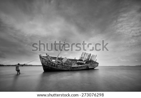 Vintage fisherman,boat Wreck Sunset light  at the beach black and white tone. - stock photo